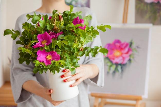 Une jeune femme floue non identifiée tient un vase dans ses mains avec une belle rose musquée à fleurs. le concept de décoration intérieure et de plantes d'élevage
