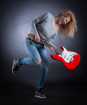 Jeune femme folle avec une composition de jazz jouant de la guitare. isolé sur un sombre