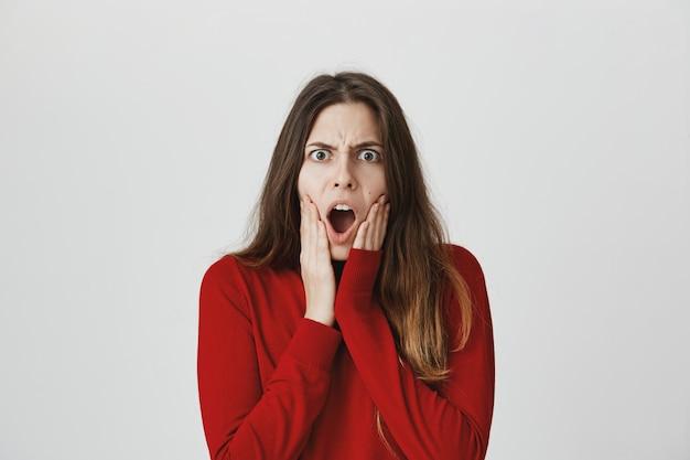 Jeune femme folle et outrée haletant choquée, bouche ouverte et fronçant les sourcils frustrée