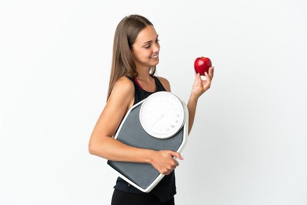 Jeune femme sur fond blanc isolé avec balance et avec une pomme