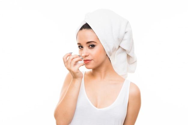Jeune femme sur fond blanc isolé avec une crème hydratante