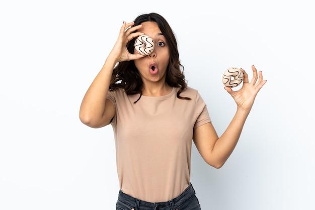 Jeune femme sur fond blanc isolé tenant un beignet dans un oeil