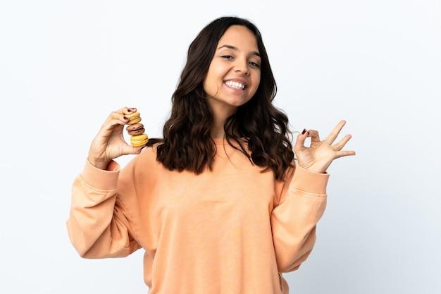Jeune femme sur fond blanc isolé tenant des macarons français colorés et montrant un signe ok avec les doigts