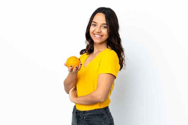 Jeune femme sur fond blanc isolé tenant une orange