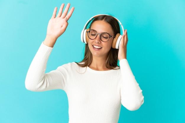 Jeune femme sur fond bleu isolé à l'écoute de la musique et de la danse