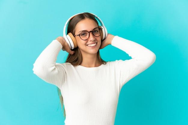 Jeune femme sur fond bleu isolé à l'écoute de la musique