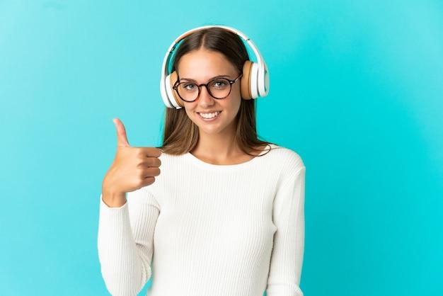 Jeune femme sur fond bleu isolé, écouter de la musique et avec le pouce vers le haut