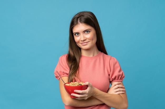 Jeune femme sur fond bleu isolé, tenant un bol de céréales