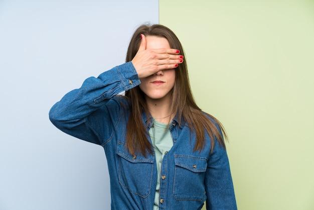 Jeune femme sur fond coloré couvrant les yeux par des mains