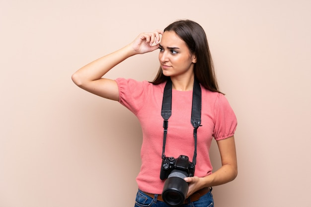 Jeune femme sur fond isolé avec une caméra professionnelle et pensant
