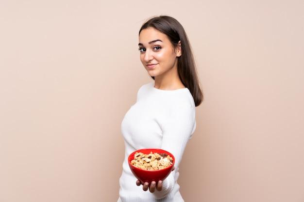 Jeune femme sur fond isolé tenant un bol de céréales
