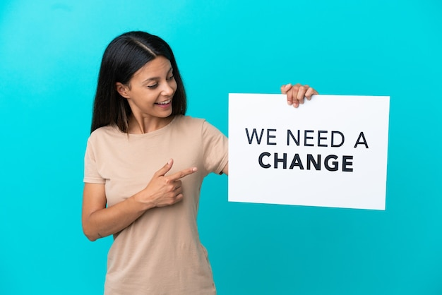 Jeune femme sur fond isolé tenant une pancarte avec du texte nous avons besoin d'un changement et le pointant