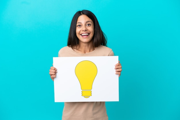 Jeune femme sur fond isolé tenant une pancarte avec une icône d'ampoule avec une expression heureuse