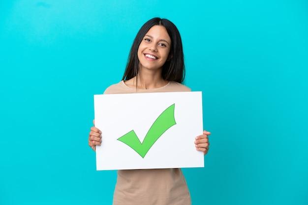 Jeune femme sur fond isolé tenant une pancarte avec l'icône de coche verte de texte avec une expression heureuse