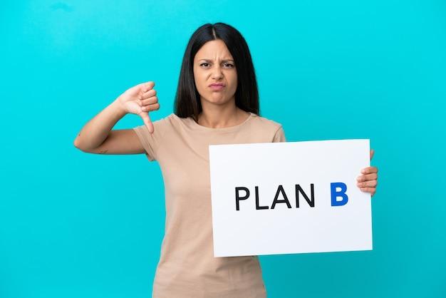 Jeune femme sur fond isolé tenant une pancarte avec le message plan b et faisant un mauvais signal