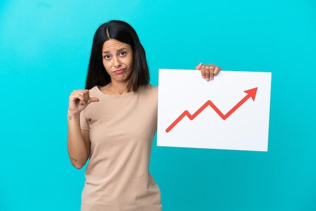 Jeune femme sur fond isolé tenant une pancarte avec un symbole de flèche de plus en plus statistique avec un geste fier