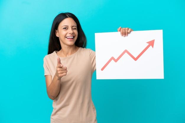 Jeune femme sur fond isolé tenant une pancarte avec un symbole de flèche de statistiques croissantes et pointant vers l'avant