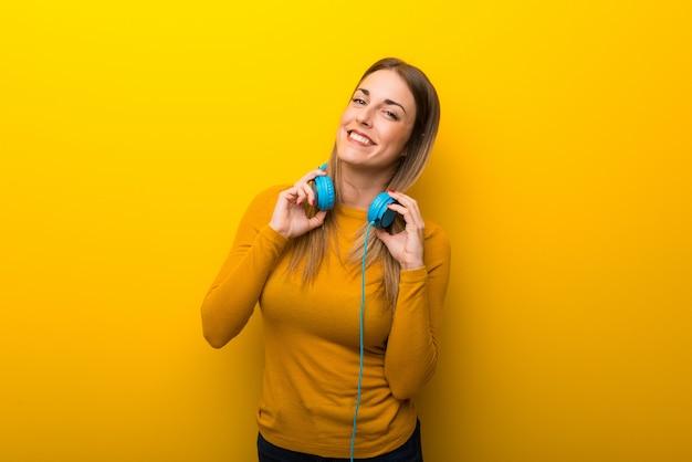 Jeune femme sur fond jaune avec un casque