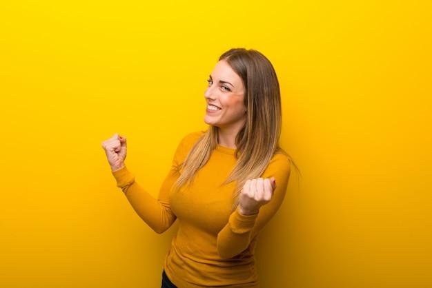 Jeune femme sur fond jaune célébrant une victoire