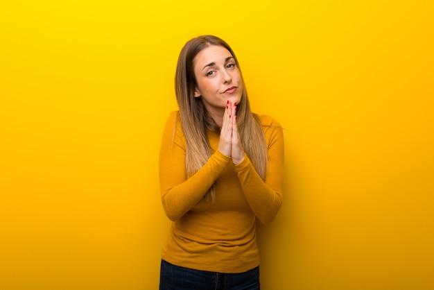 Jeune femme sur fond jaune garde la paume ensemble. personne demande quelque chose