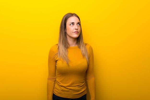 Jeune femme sur fond jaune en levant avec visage sérieux