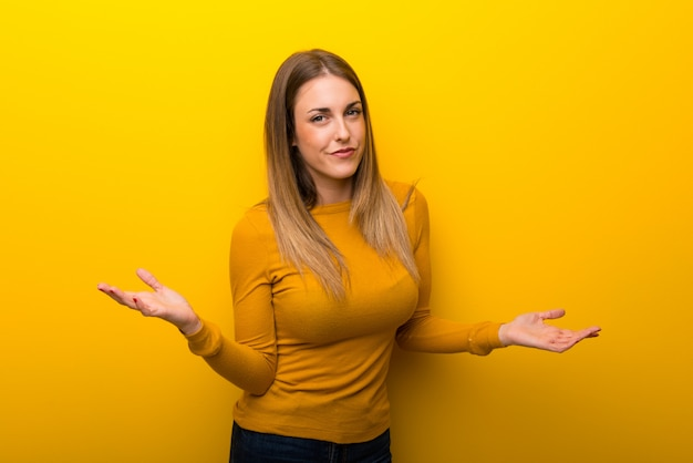 Jeune femme sur fond jaune malheureuse et frustrée par quelque chose parce que ne comprend pas quelque chose