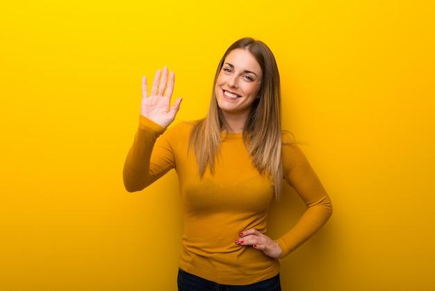 Jeune femme sur fond jaune, saluant à la main avec une expression heureuse