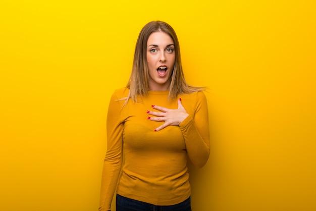 Jeune femme sur fond jaune surprise et choquée en regardant à droite