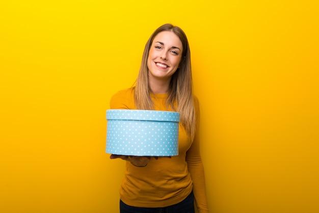 Jeune femme sur fond jaune tenant un cadeau dans les mains