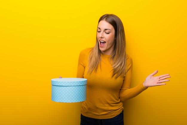 Jeune femme sur fond jaune, tenant sa boîte cadeau en mains