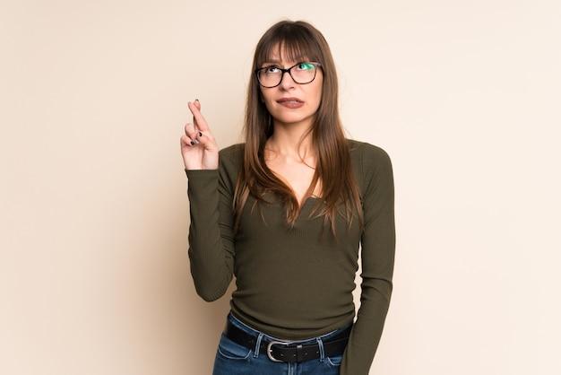 Jeune femme sur fond ocre avec les doigts qui se croisent et souhaitant le meilleur