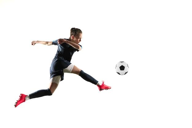 Jeune femme footballeur ou joueur de football aux cheveux longs en vêtements de sport et bottes botter le ballon pour le but en saut isolé sur fond blanc. concept de mode de vie sain, sport professionnel, passe-temps.