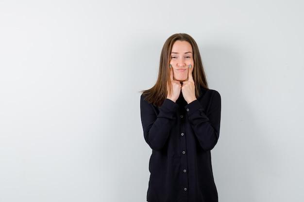 Jeune femme forçant un sourire sur le visage avec les doigts