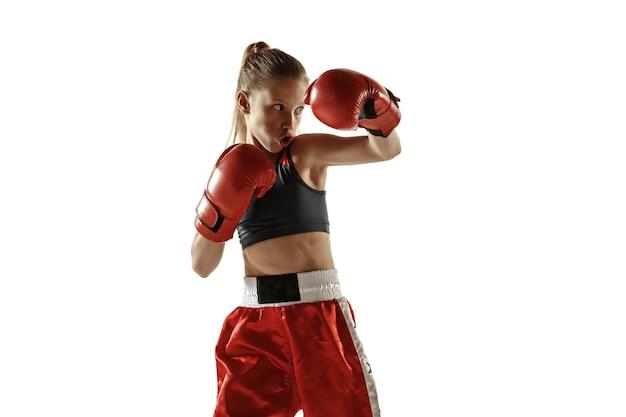 Jeune femme en formation de combat de kickboxing isolé sur fond blanc