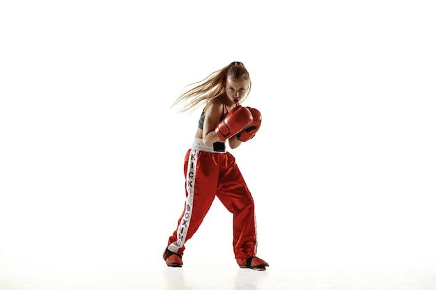 Jeune femme en formation de combattant de kickboxing isolée sur un mur blanc. fille blonde caucasienne en vêtements de sport rouges pratiquant les arts martiaux. concept de sport, mode de vie sain, mouvement, action, jeunesse.