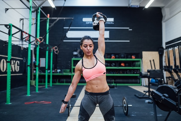 Jeune femme formation swinging kettlebell à l'intérieur dans un gymnase crossfit