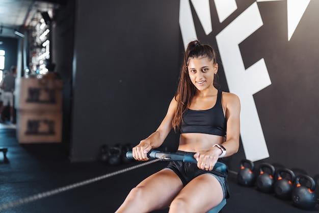 Jeune femme formation et tirant des poids dans la machine à rangée de câbles assis.