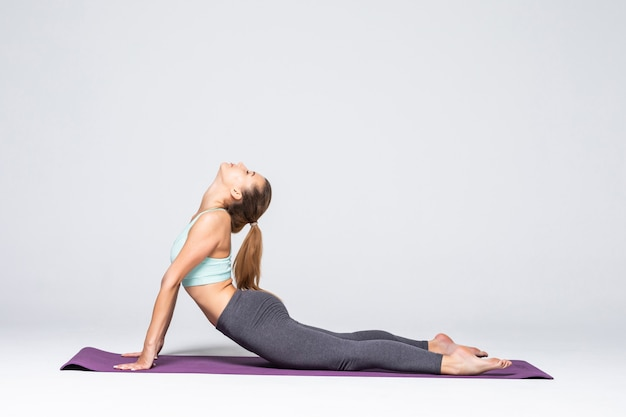 Jeune femme en forme au cours de yoga. jolie femme brune avec queue de cheval pratiquant le yoga. concept de mode de vie et de sport sain. série de poses d'exercice isolées.
