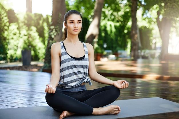 Jeune femme en forme ayant la pratique du yoga le matin assis sur un tapis dans le temple à la recherche de caméra