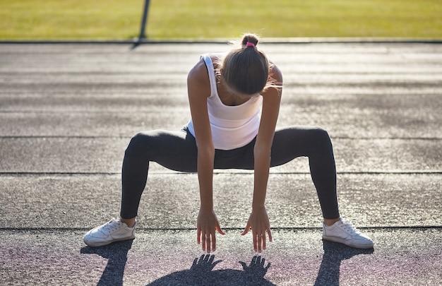 Jeune femme en forme de coureur qui s'étire avant les exercices à l'extérieur