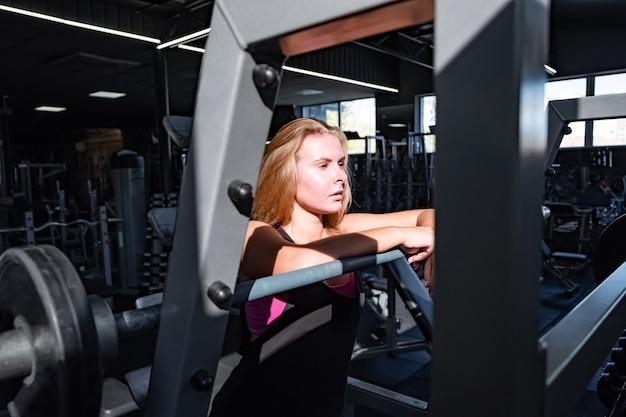 Jeune femme en forme debout dans la salle de sport en face d'haltères. portrait d'athlète féminine dans une salle de fitness parmi de nombreux équipements de fitness