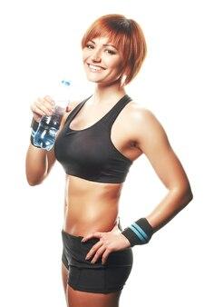 Jeune femme en forme debout et regardant la caméra, portant des sangles avec une bouteille d'eau. isolé, fond blanc, tourné en studio.