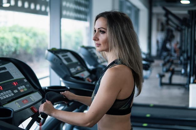 Jeune femme en forme faisant des exercices de course dans une salle de sport au tapis roulant speedwalk running road.