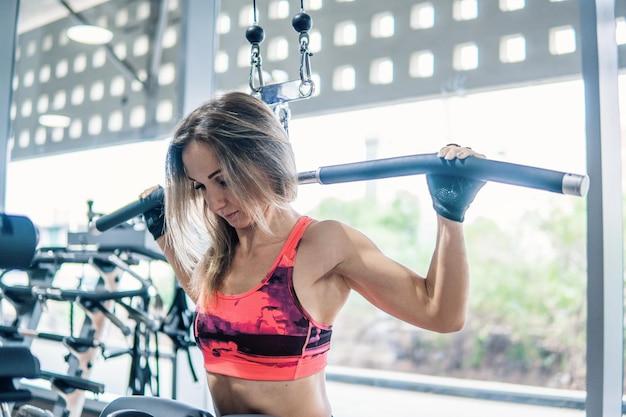 Jeune femme en forme faisant des exercices d'épaules à l'aide d'une machine d'entraînement dans une salle de sport. vue de dos.