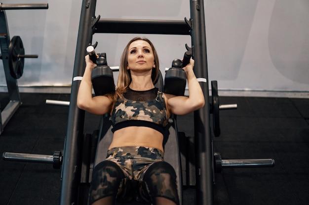Jeune femme en forme faisant des exercices de jambe à l'aide d'une machine d'entraînement dans une salle de sport. vue de l'avant