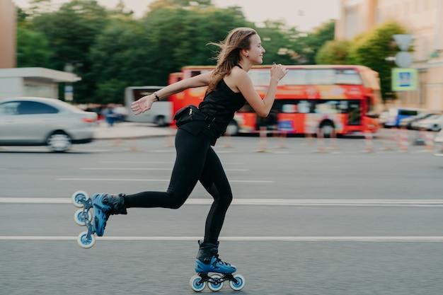 Une jeune femme en forme sur des patins à roulettes avec des patins à roues alignées pendant la journée d'été sur une route très fréquentée avec des transports mène un mode de vie actif porte des vêtements de sport noirs respire l'air frais. notion de mouvement.