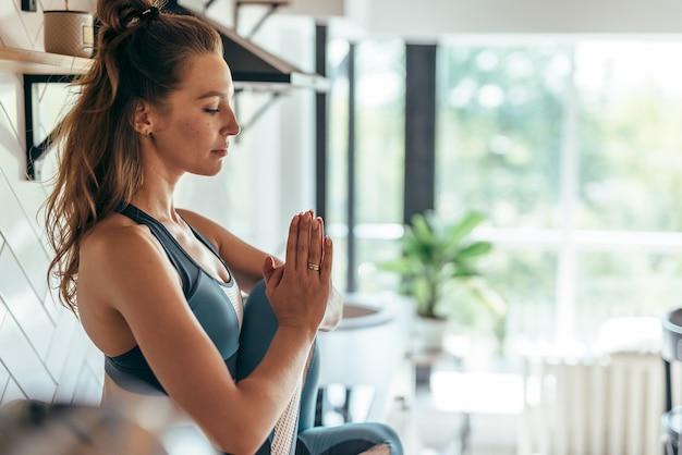 Jeune femme en forme pratiquant le yoga à la maison.