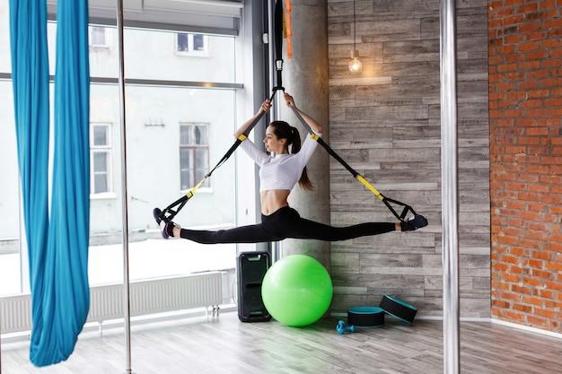 Jeune femme en forme s'étire, poussez et tirer sur les anneaux de gymnastique dans la salle de gym