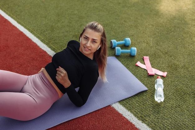 Une jeune femme en forme se repose allongée sur le tapis et écoute de la musique. entraînement extérieur. remise en forme, concept sportif. mode de vie sain