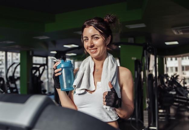 Jeune femme en forme avec une serviette sur ses épaules tenant une bouteille d'eau sur un tapis roulant. concept de perte de poids, entraînement aérobie